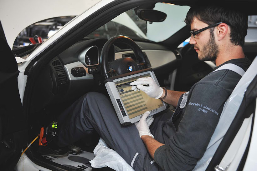 full image of one of the technicians in servin kalamatas workshop working on a bmw car